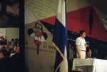 Nicaraguan man speaking in front of Sandinista flag, revolutionary wall art